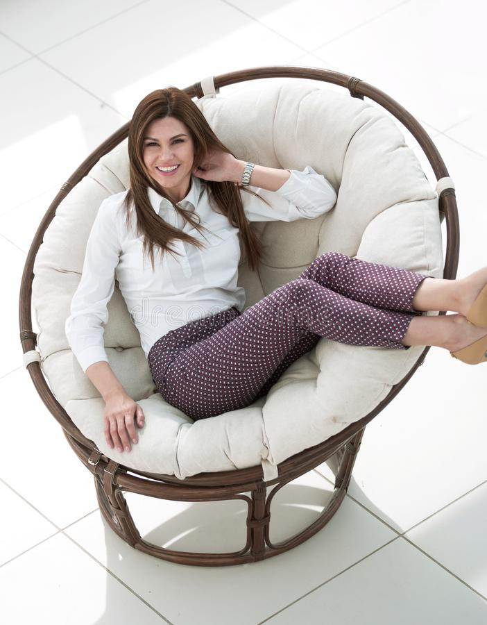 Smiling woman sitting in comfortable round chair royalty free stock images