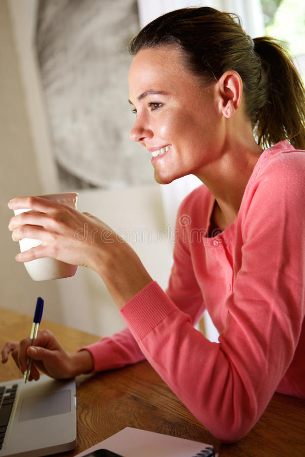 Smiling woman sitting with a cup of coffee stock images