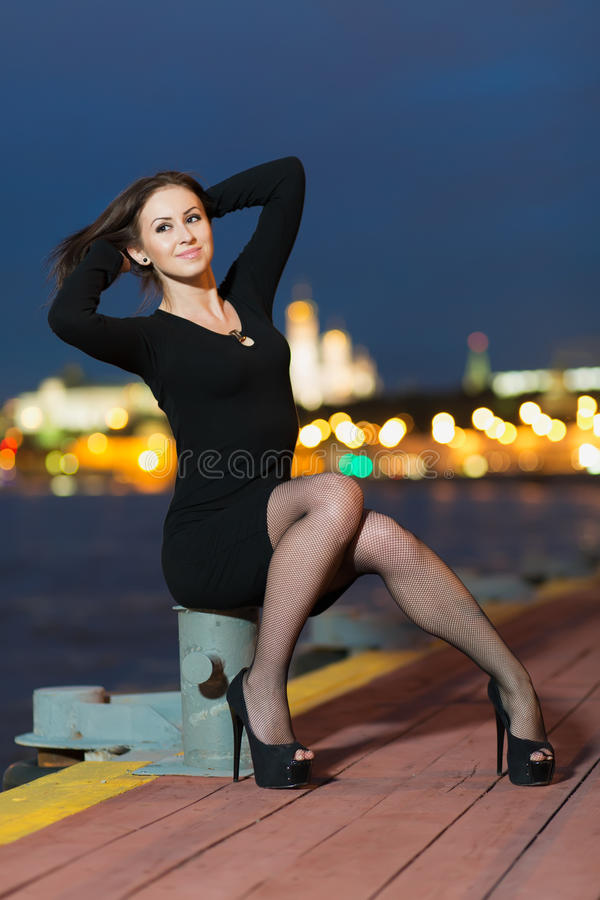 Smiling woman is sitting on device for mooring of vessels. Smiling young woman is sitting on the device for the mooring of vessels on the waterfront in the stock photos