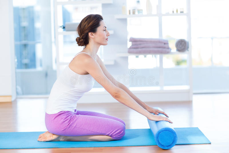 Smiling woman sitting on exercise mat stock photography