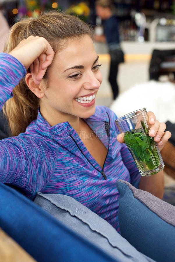 Smiling woman sitting and holding glass of fresh mint tea royalty free stock photos