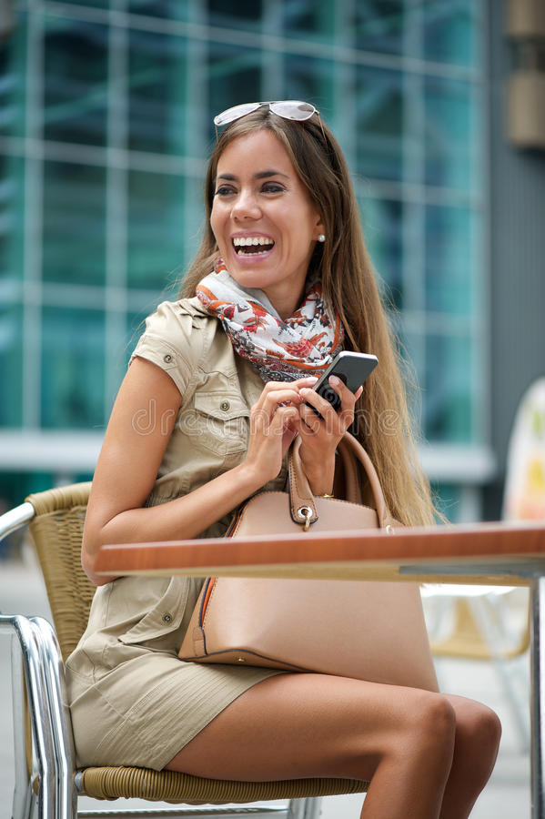 Smiling woman sitting with mobile phone royalty free stock images