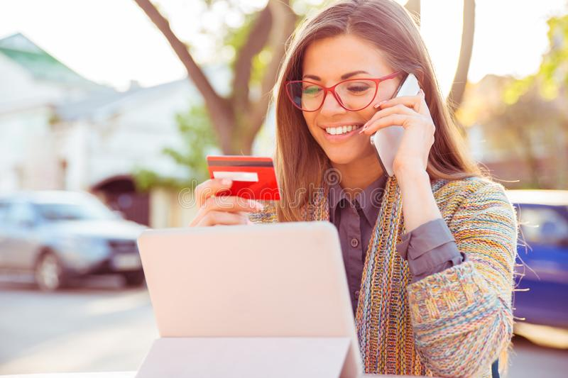 Smiling woman sitting outdoors talking on mobile phone making online payment on her tablet computer. Outside on a sunny autumn day stock image