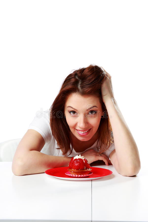 Smiling woman sitting at the table with fresh strawberry cake. Isolated on a white background stock image