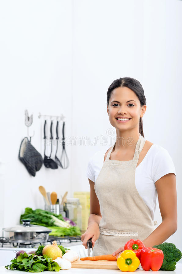 Smiling woman slicing vegetables in a kitchen royalty free stock image
