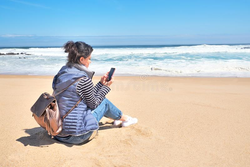Smiling woman with smartphone and backpack relaxing on beach, summer day royalty free stock images
