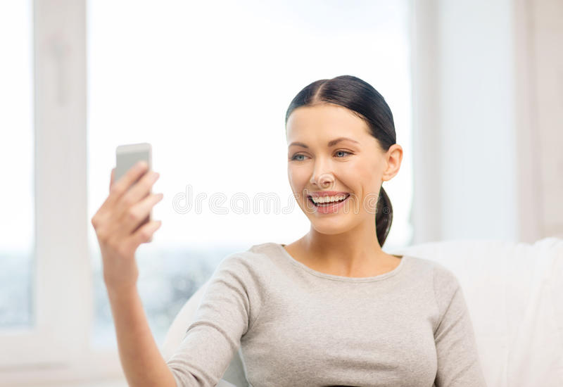 Smiling woman with smartphone at home. Home, technology, photography and internet concept - woman taking picture of herself with smartphone camera royalty free stock image