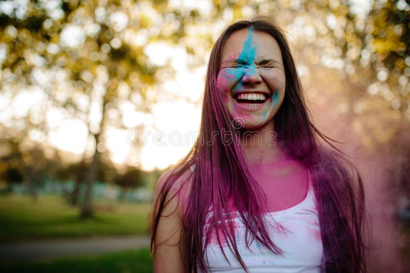 Smiling woman smeared in colors stock images