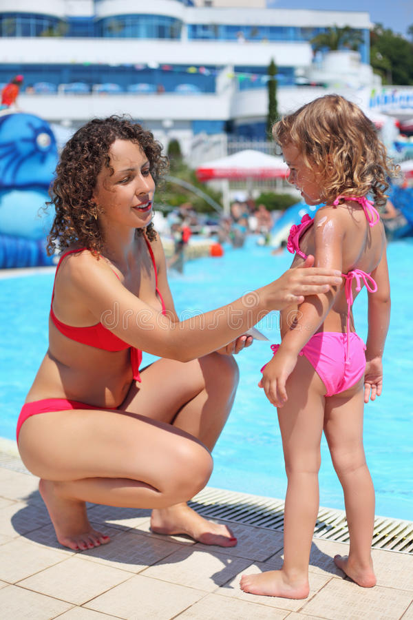 Smiling woman smears with cream for sunburn girl. Smiling beautiful woman smears with cream for sunburn little girl near pool in aquapark stock image