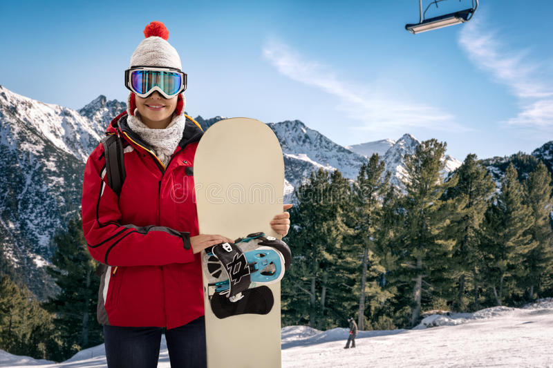 Smiling woman in snowy mountains, extreme sport and winter holiday. Young beautiful woman with ski mask holding her snowboard at ski slope stock photos