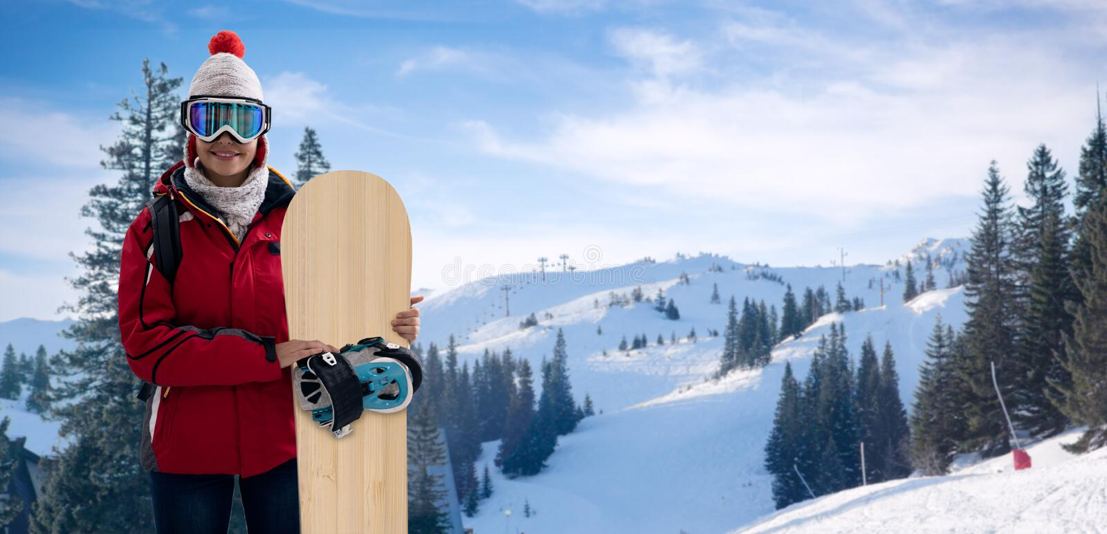 Smiling woman in snowy mountains, extreme sport and winter holiday. Young beautiful woman with ski mask holding her snowboard at ski slope royalty free stock photography