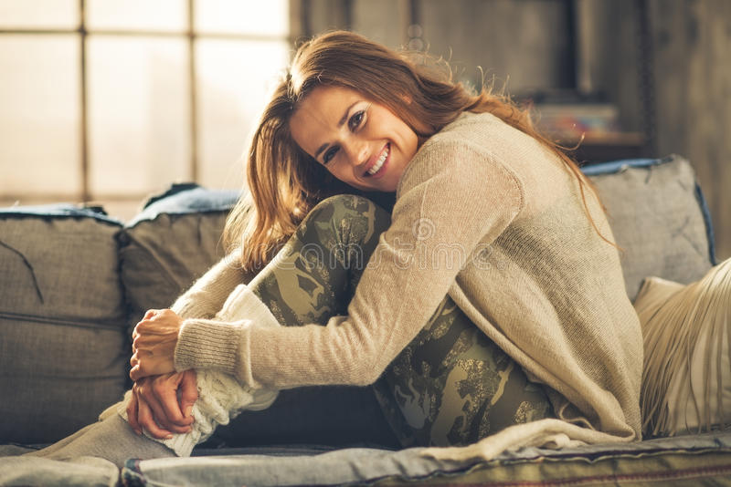 Smiling woman on sofa in loft, hugging her knees. An elegant brunette woman is smiling, hugging her knees. Wearing comfortable, casual clothing, leggings, and a stock image