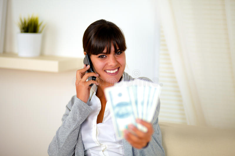 Smiling woman speaking on cellphone with money stock photos