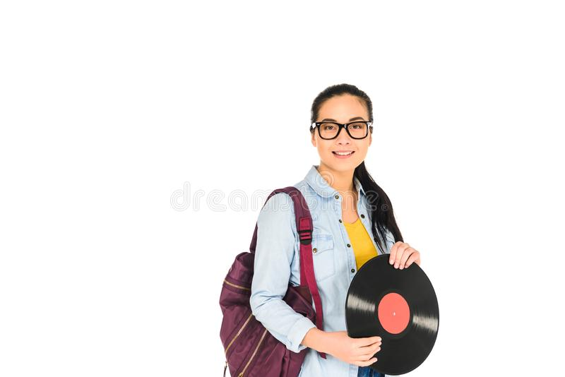 Smiling woman standing with backpack and holding vinyl record in hands isolated. On white royalty free stock photography