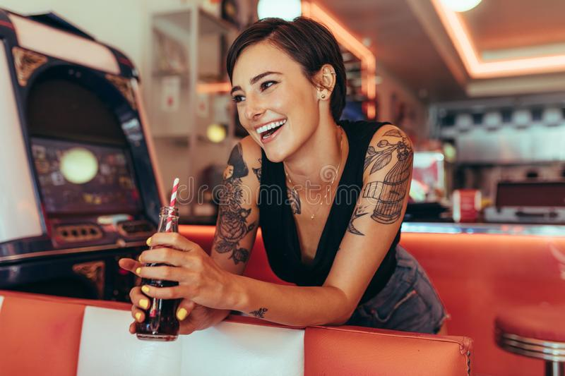 Woman standing beside a gaming machine at a diner holding a soft stock images