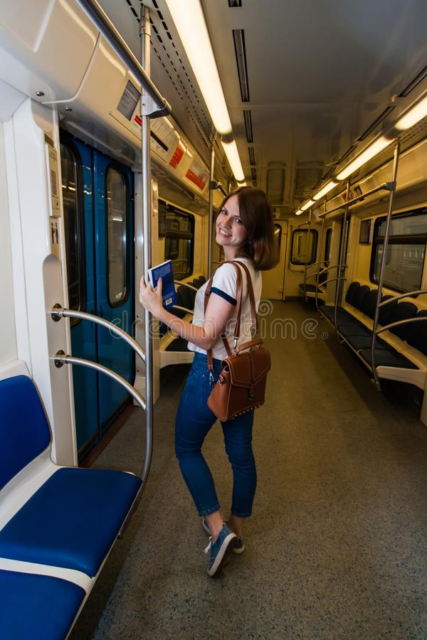 Smiling girl standing in subway train at metro stock images