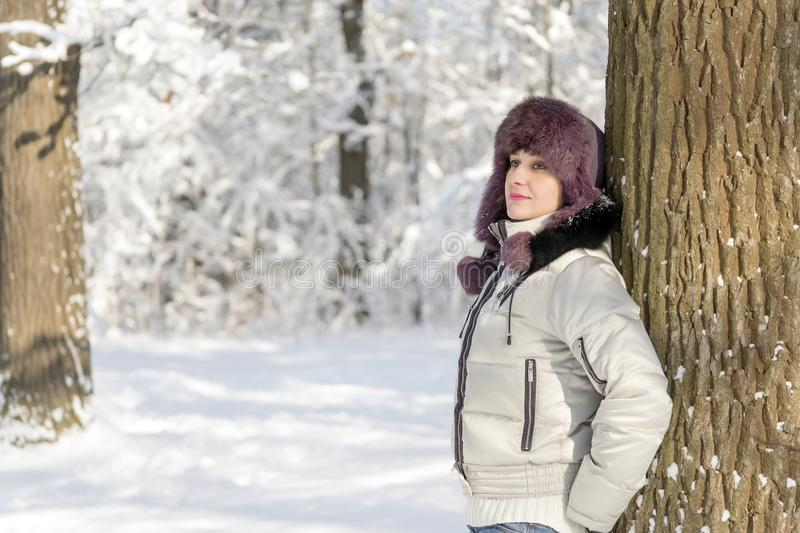 A smiling woman is standing in the forest wearing a fur hat and. A white jacket. Winter snow. The sun shines. Day, Russia stock photography