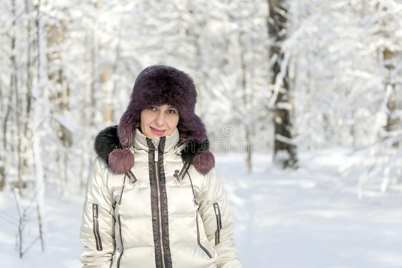 A smiling woman is standing in the forest wearing a fur hat and. A white jacket. Winter snow. The sun shines. Day, Russia stock images