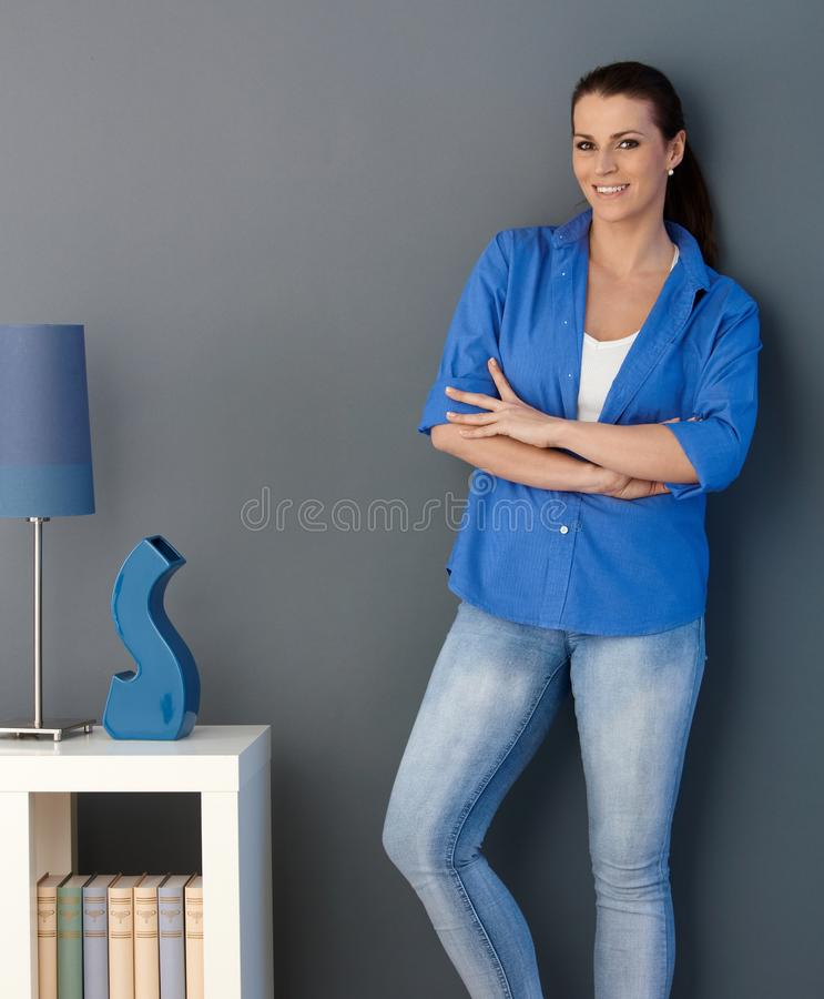 Smiling woman standing at living room wall. Smiling woman standing at design living room wall with arms crossed, looking at camera stock photos