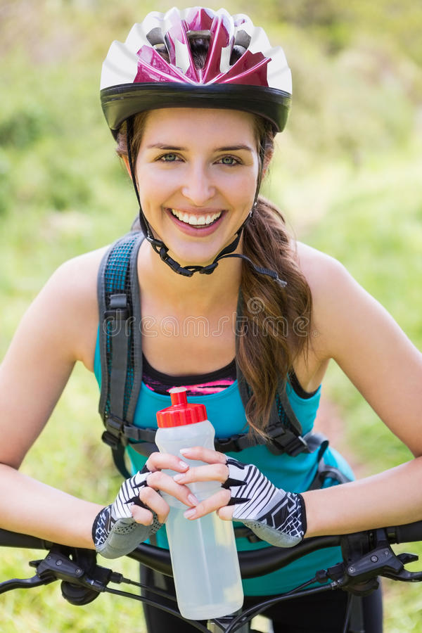 Smiling woman standing next to her bike royalty free stock photo