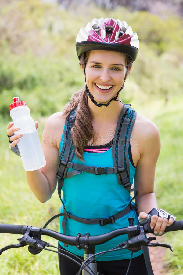Smiling woman standing next to her bike stock photos