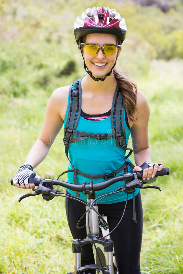 Smiling woman standing next to her bike stock image