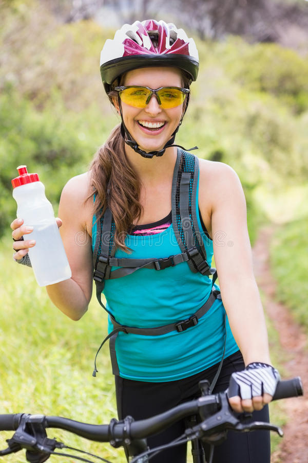Smiling woman standing next to her bike stock images