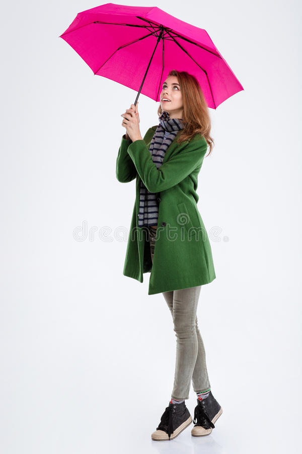Smiling woman standing with pink umbrella. Full length portrait of a smiling woman standing with pink umbrella and looking up isolated on a white background stock image
