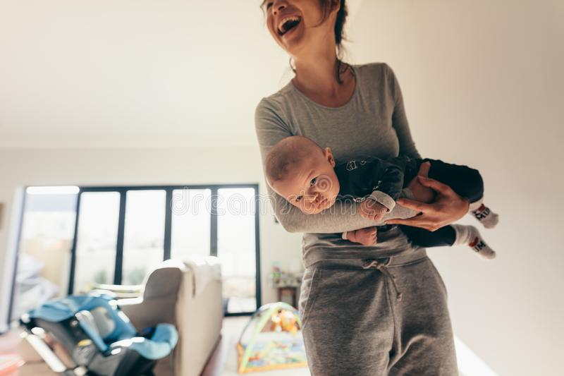 Smiling woman standing in room with her baby stock images