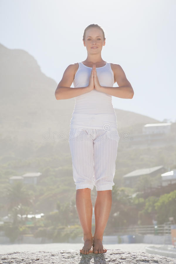 Download Smiling Woman Standing In Tree Pose On Beach Stock Photo - Image: 42528178