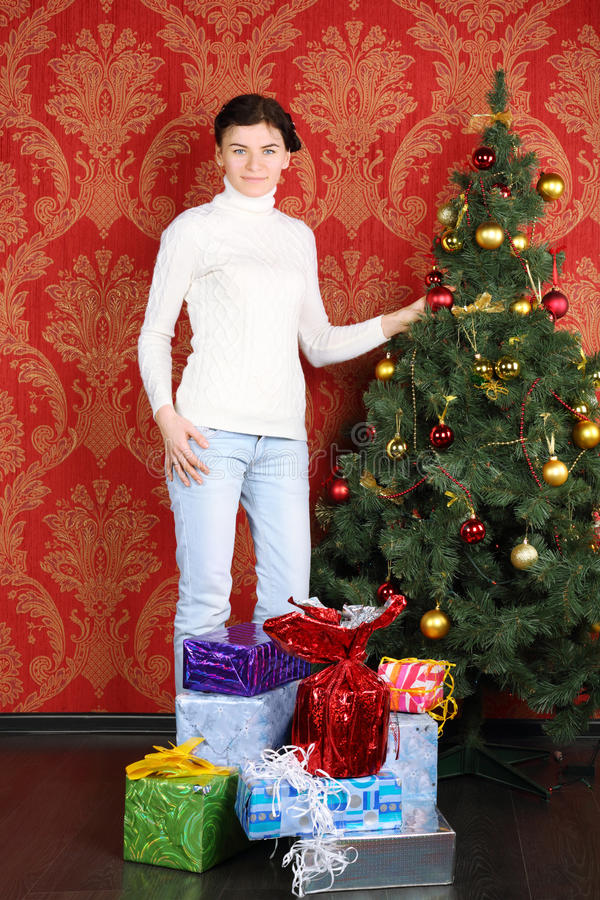 Smiling woman stands among gifts near Christmas tree. At home stock photos