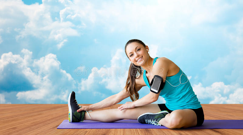 Smiling woman stretching leg on mat over clouds stock images