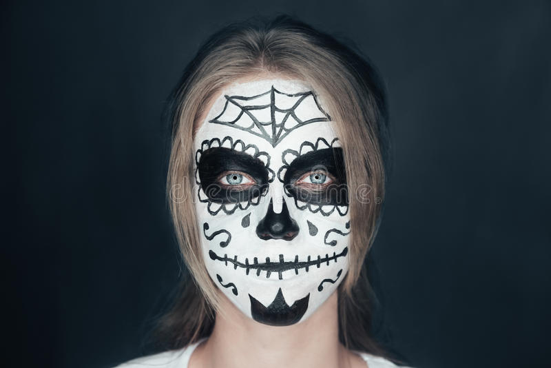 Smiling woman with sugar skull makeup. Portrait of smiling young woman with sugar skull makeup. Halloween face art stock photography