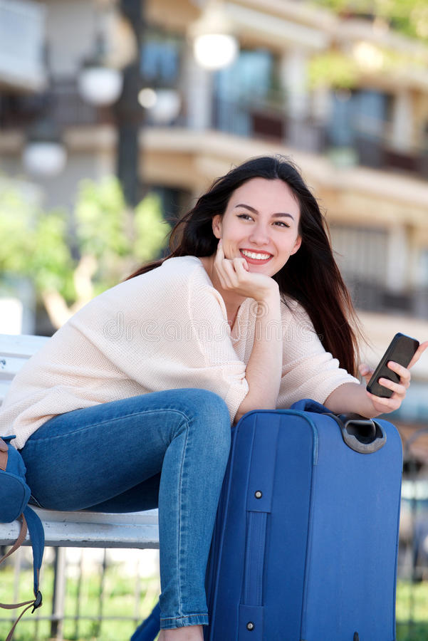 Smiling woman with suitcase and cellphone sitting on park bench royalty free stock photos