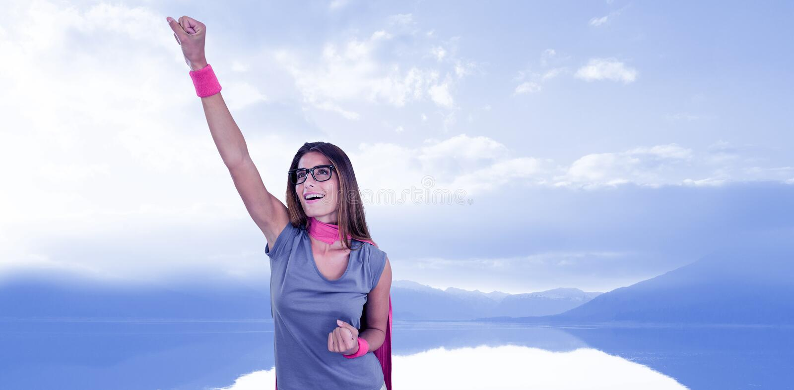 Composite image of smiling woman in superhero costume with arm raised stock photography