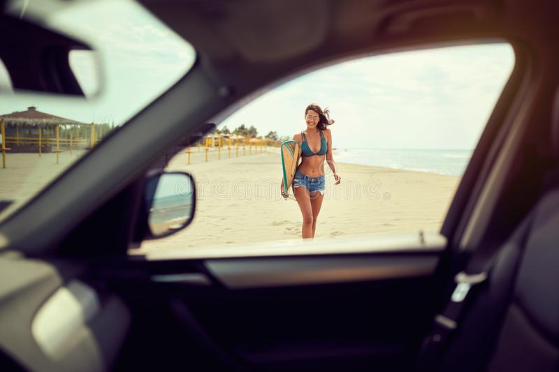 Smiling woman surfer girl in bikini with surfboard on the beach royalty free stock photos