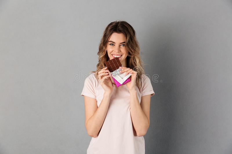 Smiling woman in t-shirt eating chocolate and looking at camera royalty free stock photography