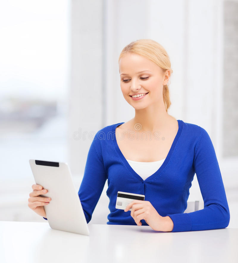 Smiling woman with tablet pc and credit card. Online shopping and technology concept - smiling young woman with tablet pc computer and credit card royalty free stock photos
