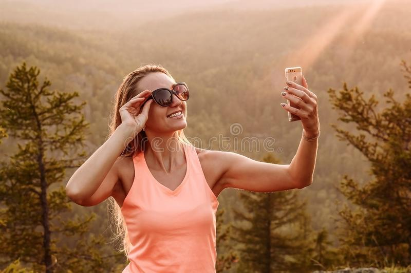 Smiling woman taking a selfie in the mountains in the summer. Selfie at sunset in summer royalty free stock photos