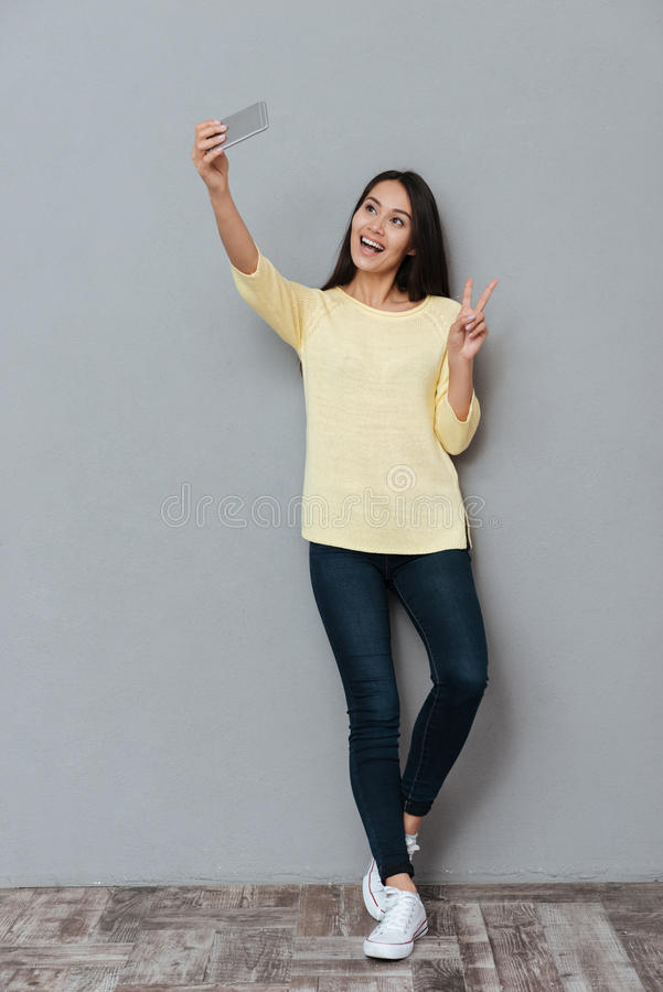 Smiling woman taking selfie with smartphone and showing peace sign. Smiling cute young woman taking selfie with smartphone and showing peace sign over grey royalty free stock image
