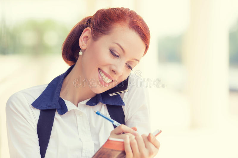 Smiling woman talking on mobile phone taking notes. Portrait headshot young happy smiling woman talking on mobile phone taking notes outside corporate office stock image