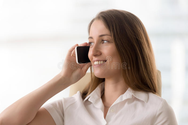 Smiling woman talking on the phone, making answering call, portr. Smiling young businesswoman talking on the phone, happy woman holding cellphone making stock image