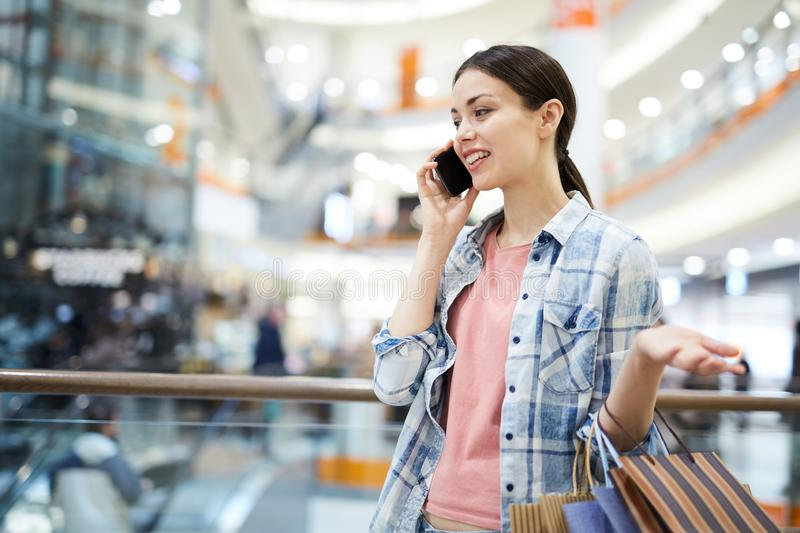 Smiling woman talking on phone in mall royalty free stock images