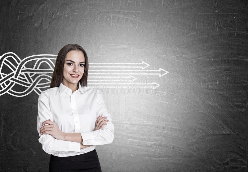 Smiling woman and tangled arrows straightening. Smiling brown haired woman with crossed arms is standing near a blackboard with tangled arrows straightening as stock image