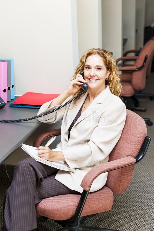 Download Smiling Woman On Telephone At Office Desk Stock Photo - Image of handset, caucasian: 32022330