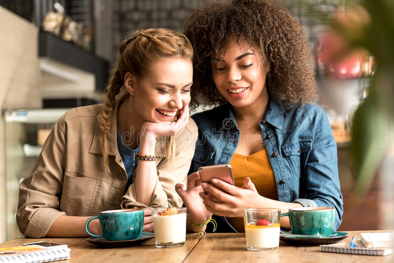 Smiling woman telling with beaming female. Outgoing girl speaking with cheerful african friend while sitting at table in confectionary shop. They looking at royalty free stock image