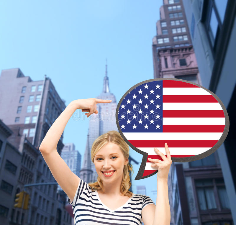 Smiling woman with text bubble of american flag. Education, foreign language, english, people and communication concept - smiling woman holding text bubble of stock photo