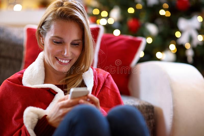 Woman texting messages on Christmas holiday stock image