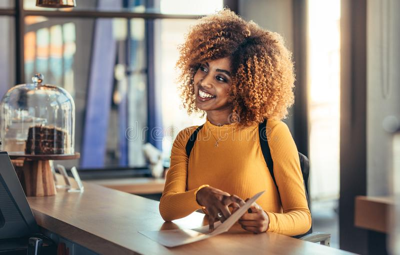 Cheerful afro american woman ordering food at a cafe royalty free stock images