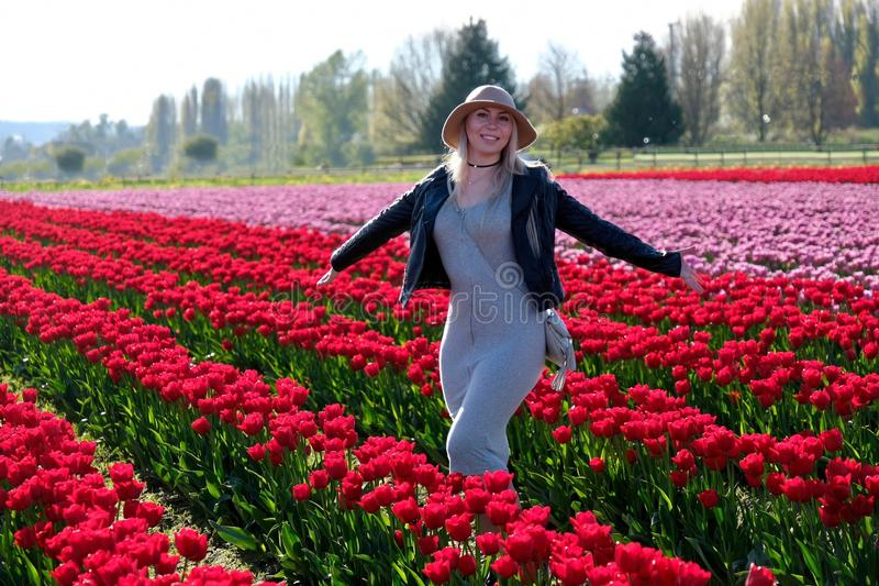 Smiling woman in tulip fields. Skagit Valley Tulip Festival. Mount Vernon. Seattle. WA. United States royalty free stock photography